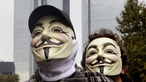Image: Protesters wear masks styled after V for Vendetta